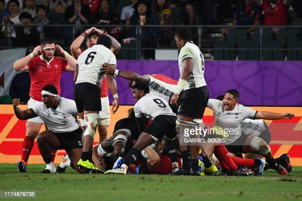 Fiji's players react after they were awarded a penalty try during the Japan 2019 Rugby World Cup Pool D match between Wales and Fiji at the Oita...