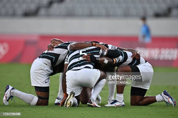 Fiji's players react after winning the men's final rugby sevens match between New Zealand and Fiji during the Tokyo 2020 Olympic Games at the Tokyo...