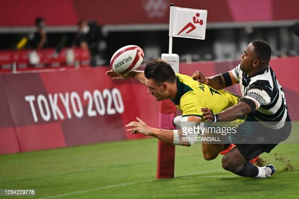 Fiji's Waisea Nacuqu defends the tryline against Australia's Lachlan Anderson in the men's quarter-final rugby sevens match between Fiji and...