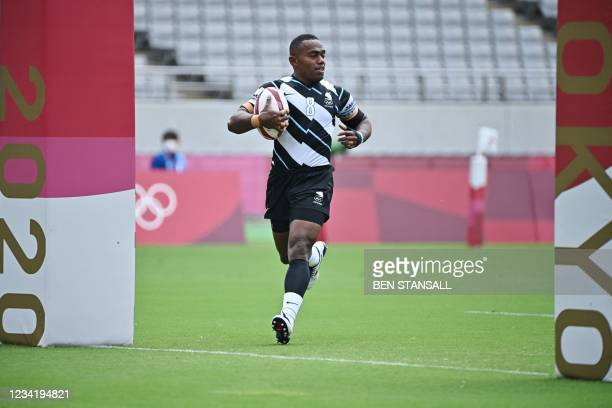 Fiji's Waisea Nacuqu scores a try in the men's pool B rugby sevens match between Fiji and Japan during the Tokyo 2020 Olympic Games at the Tokyo...
