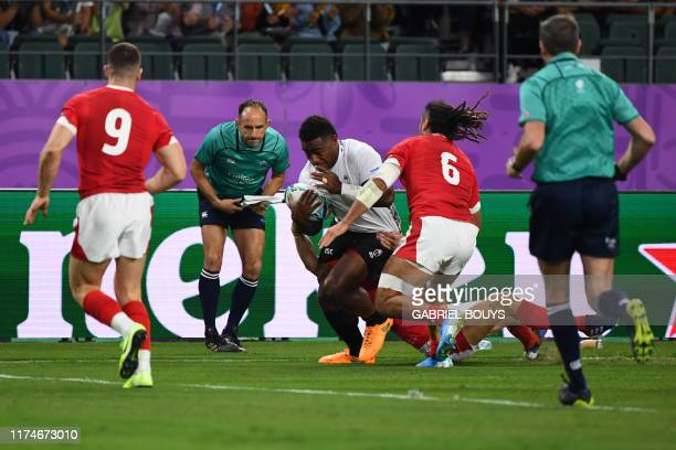 Fiji's wing Josua Tuisova runs on his way to scoring a try during the Japan 2019 Rugby World Cup Pool D match between Wales and Fiji at the Oita...