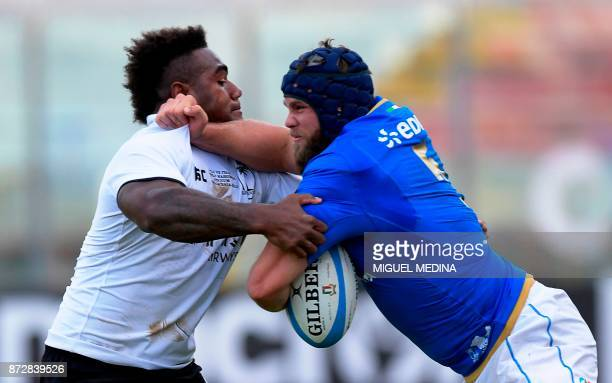 Fiji's winger Josua Tuisova vies with Italy's lock Dean Budd during a rugby union test match between Italy and Fiji at the Angelo Massimino Stadium...
