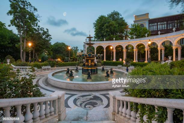 filarmonia fountain park at night next to the icheri sheher(old city), baku,azerbaijan - baku stock pictures, royalty-free photos & images