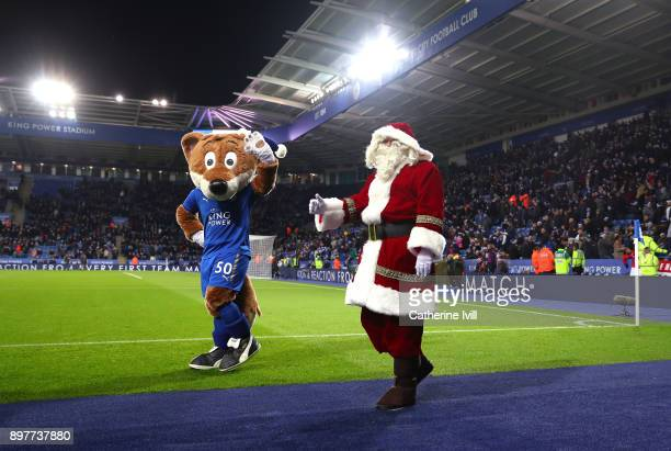 Filbert the Fox mascot of Leicester City walks pitchside with Father Christmas during the Premier League match between Leicester City and Manchester...