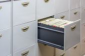 File cabinet with a wide open drawer full of files