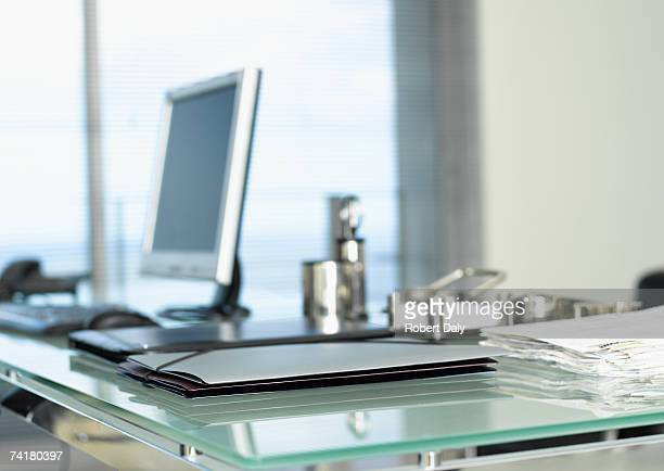 File folders with stack of paperwork on desk with computer