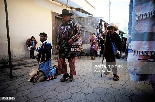 A Blind Man Begs As A Man In Traditional Clothing And A Disabled Man Pass By Him In The Market Of Chichicastenango In The Western Highlands Of...