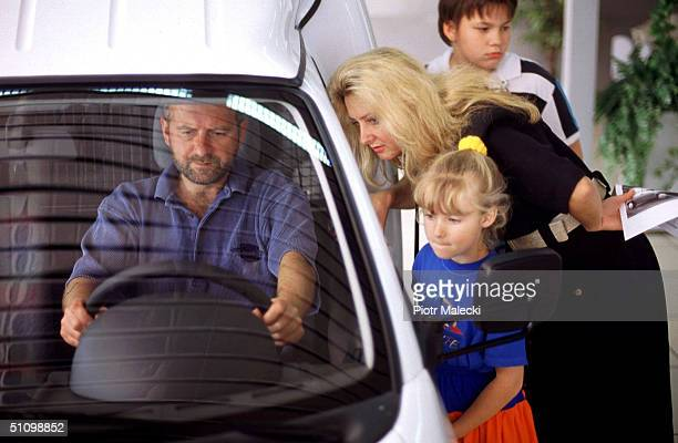 A Family Is Examines An Opel Corsa Car At The General Motors Showroom In Warsaw Poland