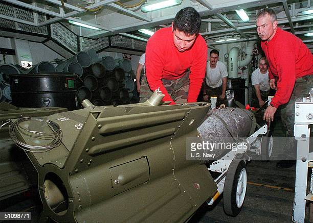 Airman Juan Duarte And Aviation Ordnanceman Cris Holton Strap Down A Gbu-16 Bomb To A Weapons Skid For Immediate Transport To The Flight Deck Of The...