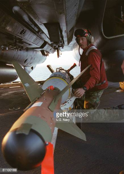 """An Aviation Ordnancemen Loads A Laser Guided Bomb Onto The Underside Of An F-14 """"Tomcat"""" In Preparation For Air Strikes From The Aircraft Carrier USS..."""