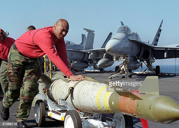 Aviation Ordnanceman Airman Bryan Broome Moves A Gbu-16 Laser Guided Bomb In Preparation For Night Air Strikes From The Aircraft Carrier USS Carl...