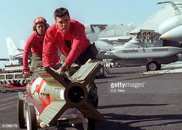 Aviation Ordnanceman Bryan Lee Pushes A Gbu-16 Laser Guided Missile As Aviation Ordnanceman Donovan Payne Steers From Behind, In Preparation For...