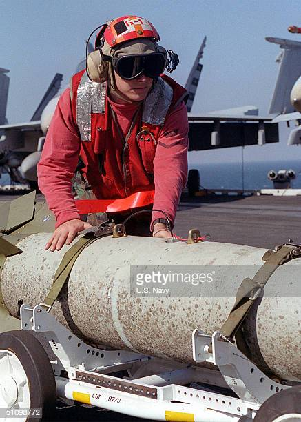 Aviation Ordnanceman Gregory Vanbrunt Moves A Gbu-16 Laser Guided Bomb In Preparation For Night Air Strikes From The Aircraft Carrier USS Carl Vinson...