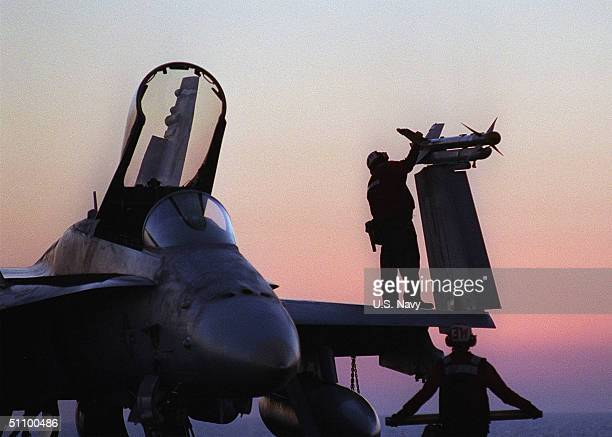 """Aviation Ordnancemen Jason Mitchell Inspects The Mounting Of A Sidewinder Missile On An F/A 18 """"Hornet"""" Aboard USS Carl Vinson December 19, 1998...."""