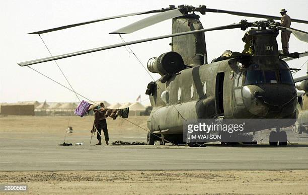 File photo dated 17 March 2003 shows a US soldier hanging his laundry on a US army Chinook helicopter 17 March 2003 at Camp Udairi in northern...