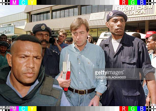 File photo dated 24 March of Sandline International chief executive Tim Spicer being escorted under heavy police guard into Boroko District Court in...