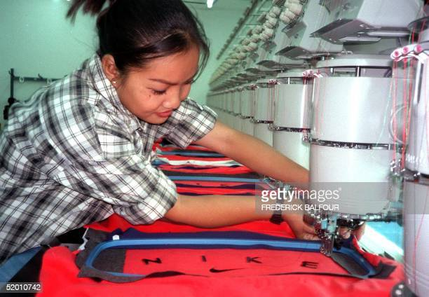 A file photo shows a female worker embroidering logos on Nike apparel in a privately owned garment factory in Vientiane 23 November 1998 The tiny...