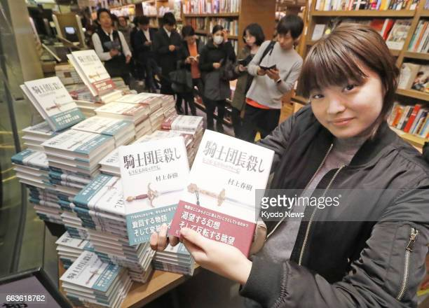 File photo shows a woman holding copies of 'Killing Commendatore' a novel by Japanese writer Haruki Murakami at a Tokyo bookstore in the early hours...