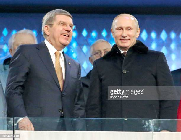 File photo shows International Olympic Committee President Thomas Bach and Russian President Vladimir Putin attending the 2014 Winter Olympics...