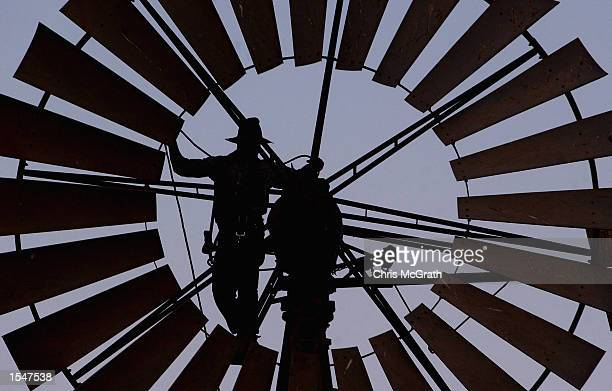 A file photo shows Pineview Station owner Mark Lacey repairing one of his broken windmills on October 25 2002 in Broken Hill New South Wales...