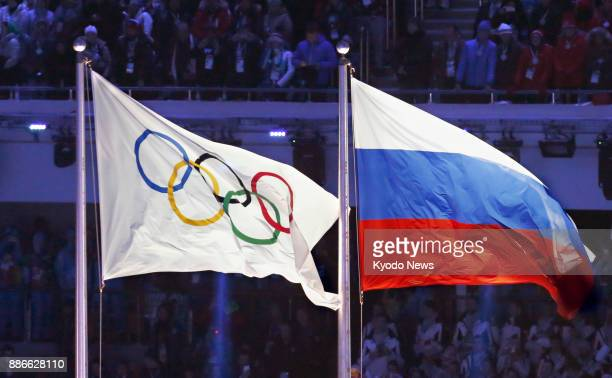 File photo shows the Olympic flag flying alongside the Russian flag at the 2014 Winter Olympics opening ceremony in Sochi Russia on Feb 7 2014 The...