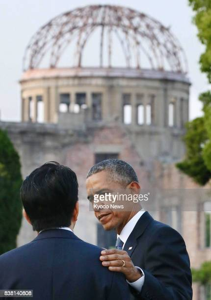 File photo shows US President Barack Obama putting his hand on the shoulder of Japanese Prime Minister Shinzo Abe at the Peace Memorial Park in...