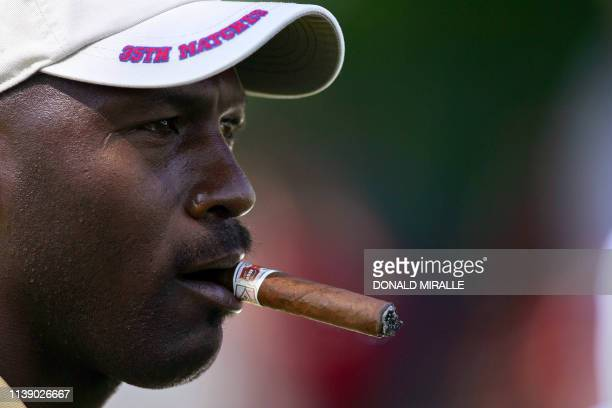 File photo taken 19 September 2004 shows US team supporter and former NBA superstar Michael Jordan smoking a cigar as he watches the play during the...