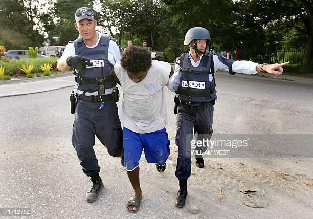 A file photo taken 20 April 2006 shows two Australian Federal policemen arresting a Solomon Islander as Australian army and police personnel arrive...