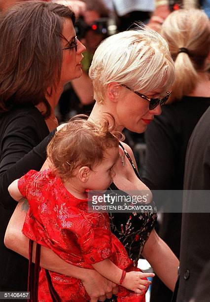 A file photo taken 27 November 1997 shows Paula Yates carrying her daughter Heavenly Hiraani Tiger Lily into the funeral in Sydney of her partner and...