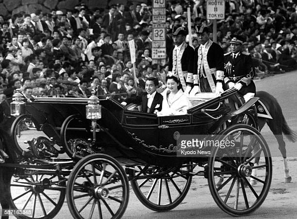 File photo taken April 10 shows thenCrown Prince Akihito and Princess Michiko parading in a carriage in Tokyo after their marriage ceremony