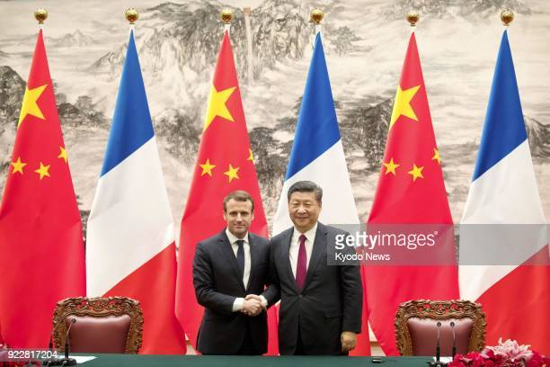 File photo taken at the Great Hall of the People in Beijing on Jan 9 shows French President Emmanuel Macron and Chinese President Xi Jinping shaking...