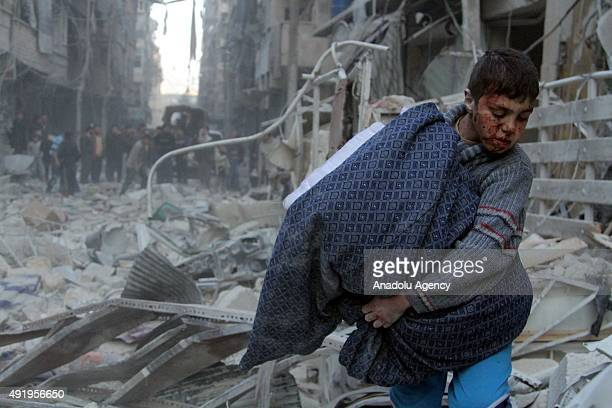 A file photo taken by AA photojournalist Saleh Mahmoud Laila shows a Syrian kid walks with remains of his house after a barrel bomb attack of Syrian...