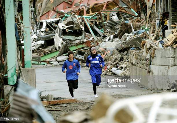File photo taken in April 2011 shows two runners jogging in downtown Onagawa in northeastern Japan's Miyagi Prefecture which was in ruins after being...