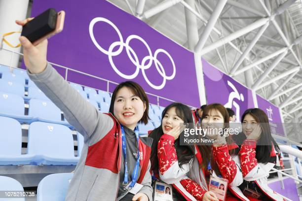 File photo taken in February 2018 shows volunteers for the 2018 Pyeongchang Winter Olympics posing for photos in Gangneung, South Korea. ==Kyodo