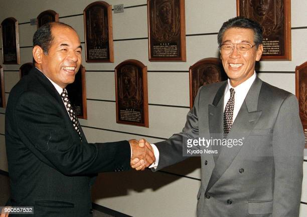 File photo taken in January 1996 shows former Hiroshima Carp player Sachio Kinugasa and former Yomiuri Giants manager Motoshi Fujita shaking hands...
