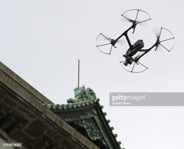 File photo taken in July 2018 shows a drone taking aerial photographs of the Aichi prefectural government office building for inspection purposes in...
