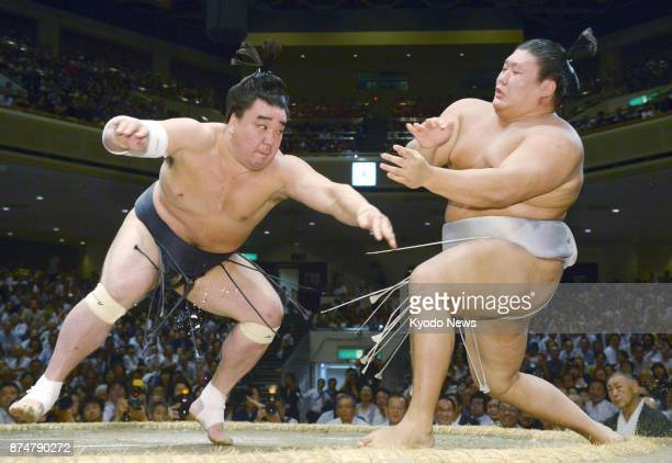 File photo taken in September 2016 shows grand champion Harumafuji and Takanoiwa facing off on the ring during a bout at the Autumn Grand Sumo...