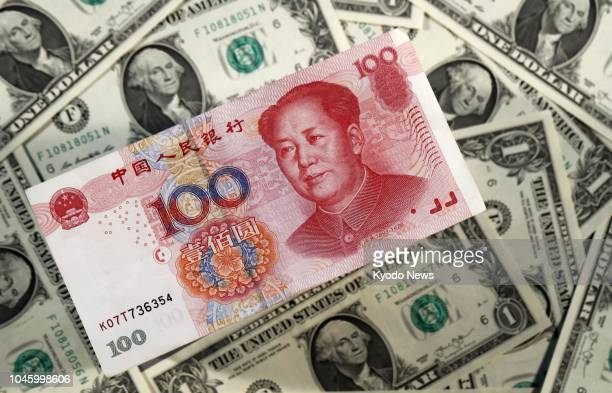 File photo taken July 5 shows a Chinese 100yuan banknote and US dollar banknotes ==Kyodo