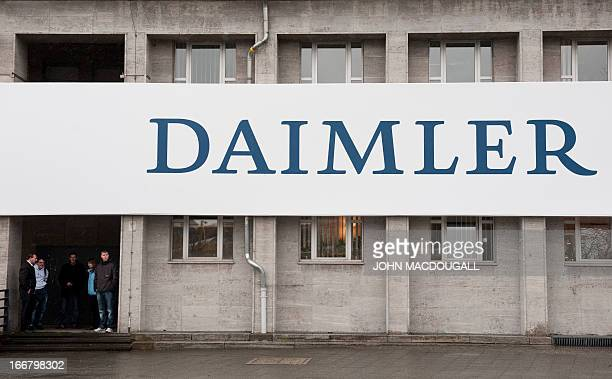 A file photo taken on April 13 2011 shows people next to a Daimler logo outside the venue of Daimler's annual shareholders meeting in Berlin German...