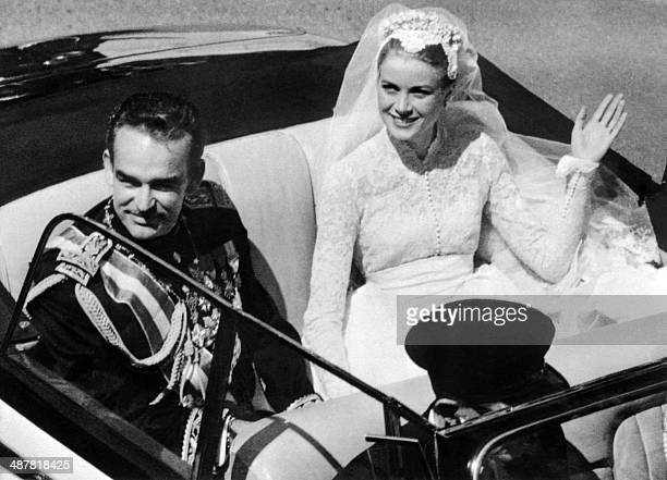 A file photo taken on April 19 1956 shows Prince Rainier III of Monaco and US actress and princess of Monaco Grace Kelly saluting the crowd as they...