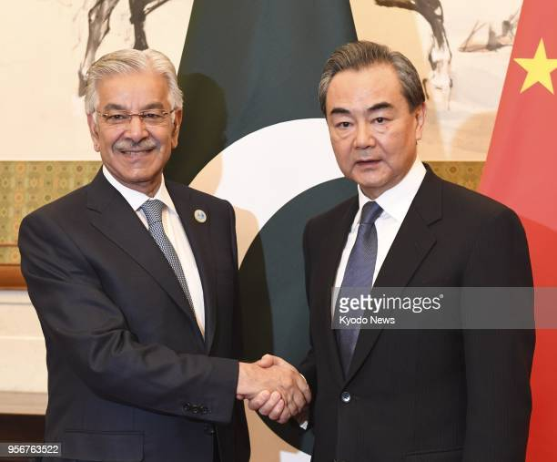 File photo taken on April 23 shows Chinese Foreign Minister Wang Yi shaking hands with his Pakistani counterpart Khawaja Asif in Beijing ==Kyodo