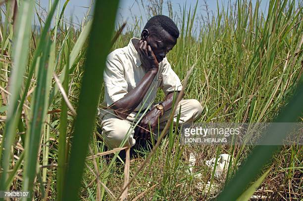 A file photo taken on February 17 2007 shows a man kneels down beside a human skull on a field in Bogoro Democratic Republic of Congo A former...