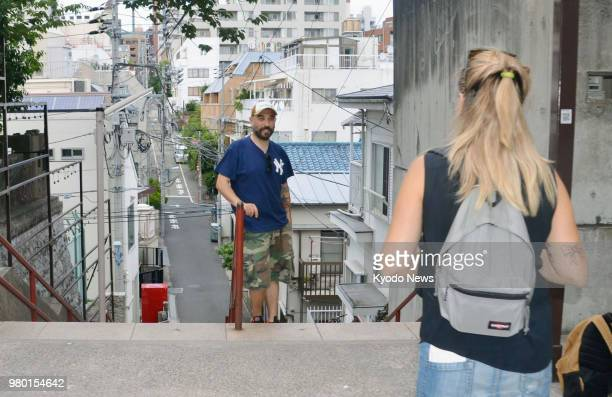 File photo taken on July 13 2017 shows foreign tourists visiting a spot in Tokyo's Yotsuya district featured in the blockbuster Japanese animation...