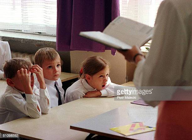 Three Children Listen To Their Teacher On The First Day At A Primary School Number In Warsaw