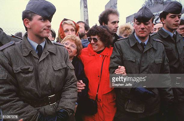 Two West German Women Hold The Arms Of Two East German Guards At The Berlin Wall During The Collapse Of Communism In East Berlin On November 12 1989...