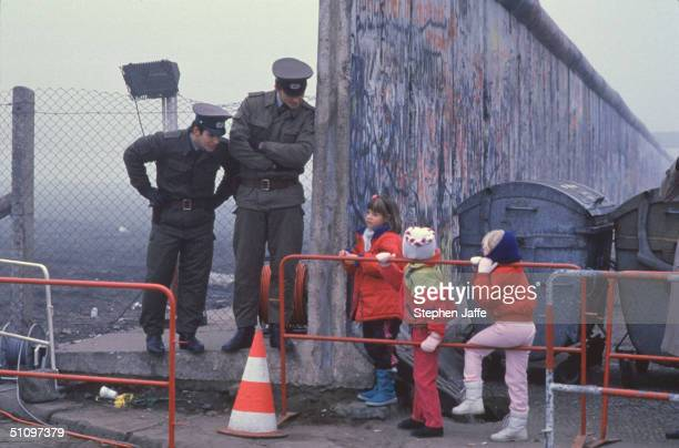 West German School Children On The Way To School Come Across The Berlin Wall Being Opened With Two East German Border Guards During The Collapse Of...