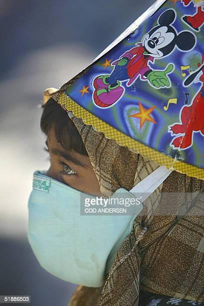 File picture dated 01 January 2004 shows a young girl with a facemask and a Mickey mouse hat watching rescue workers dig for earthquake victims in...