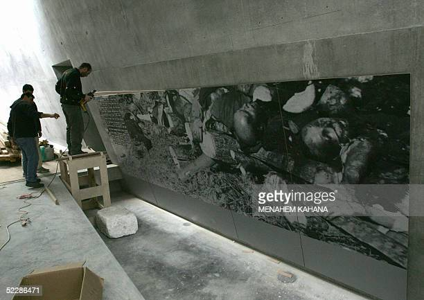 File picture dated 13 February 2005 shows workers hanging a huge picture in one of the halls of the new Holocaust History Museum at Jerusalem's Yad...