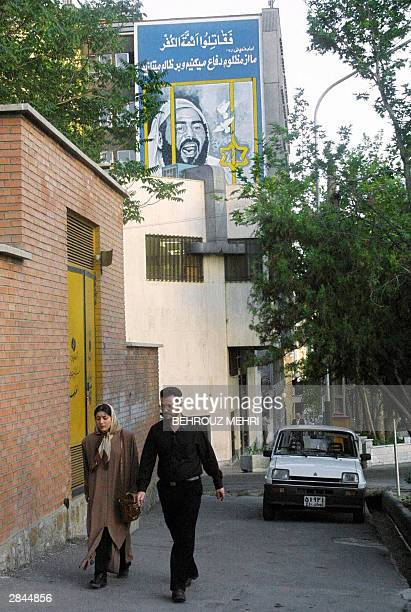 File picture dated 21 May 2001 shows an Iranian couple passing under a huge mural of Khaled Islambuli who killed Egyptian President Anwar Sadat on a...