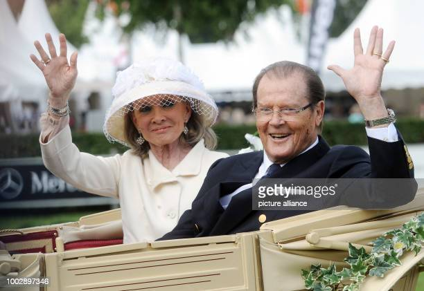 FILE File picture dated 25 June 2016 showing actor Roger Moore and his Danish wife Kristina Tholstrup riding a coach during the opening ceremony of...
